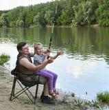 Folk som campar och fiskar, familjfritid i natur, fisk som fångas på bete, flod och skog, sommarsäsong Royaltyfri Fotografi