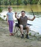Folk som campar och fiskar, familjfritid i natur, fisk som fångas på bete, flod och skog, sommarsäsong Royaltyfria Foton