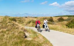 Folk som cyklar i dyn av Texel, Nederländerna Arkivfoton