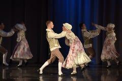 Folk som dansar i traditionella dräkter på etapp, Arkivbild