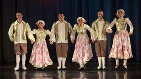 Folk som dansar i traditionella dräkter på etapp, Arkivbilder