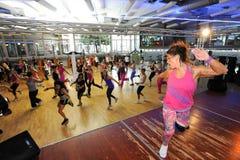 Folk som dansar under Zumba utbildningskondition på en idrottshall Royaltyfri Fotografi