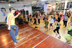 Folk som dansar under Zumba utbildningskondition på en idrottshall Royaltyfri Foto