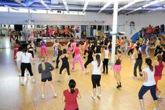 Folk som dansar under Zumba utbildningskondition på en idrottshall Arkivfoto