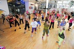 Folk som dansar under Zumba utbildningskondition på en idrottshall Arkivbild