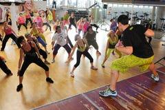 Folk som dansar under Zumba utbildningskondition på en idrottshall fotografering för bildbyråer