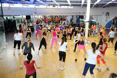 Folk som dansar under Zumba utbildningskondition på en idrottshall Royaltyfria Bilder