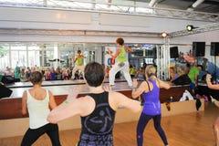 Folk som dansar under Zumba utbildningskondition på en idrottshall royaltyfri bild