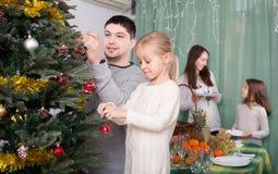 Folk som dekorerar julgranen Arkivbild
