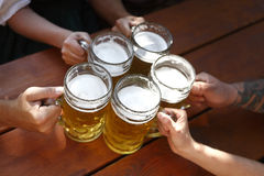 Folk som dricker öl i en traditionell bayersk ölträdgård