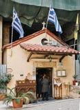 Folk som enetering i liten kyrka i mitten av Aten Arkivbild