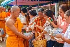 Folk som erbjuder klibbiga ris till munkar i morgonen Arkivbild