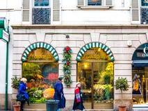 Folk som förbigår en blomsterhandel Arkivbild