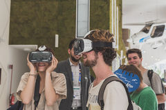 Folk som försöker hörlurar med mikrofon 3D på expon 2015 i Milan, Italien Royaltyfri Foto