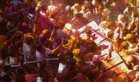 Folk som firar holi festivalen av färger inom en tempel, royaltyfri fotografi