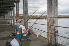 Folk som fiskar från lägre nivå av Whitby West Pier North Yorksh arkivbild