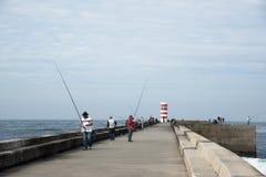 Folk som fiskar i framdel av fyren Royaltyfria Bilder