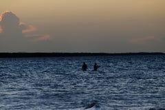 Folk som fiskar i havet på solnedgången royaltyfria bilder