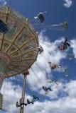 Folk som flyger i cirklar mot blåa molniga himlar Royaltyfri Bild