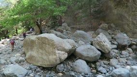 Folk som fotvandrar till och med Samaria Gorge på Kreta Grekland Skugga att leda till och med de Lefka Ori bergen in mot havet stock video