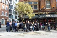 Folk som framme dricker av en typisk bar i det London centret Arkivbild