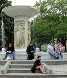 Folk som framme kopplar av av Daniels Chester Frenchs marmorspringbrunnen i mitten av den Du Pont cirkeln i Washington DC royaltyfria foton