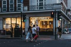 Folk som framme korsar vägen av Pret en krubba i London, UK royaltyfri fotografi