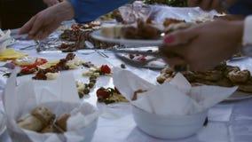 Folk som fyller deras plattor med mat på en svensk tabell stock video