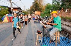 Folk som går förbi en gitarrist som spelar musik på gatamässan arkivbilder