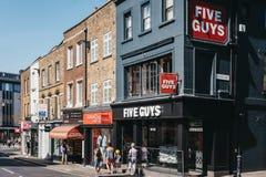 Folk som går förbi restaurang för fem grabbar i Richmond, London, UK arkivbild