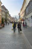 Folk som går i den gamla staden av Brasov Arkivbild