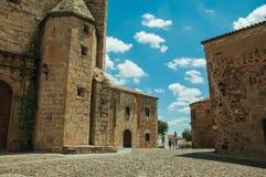Folk som går i en kullerstengränd under gotiska byggnader på Caceres arkivbild