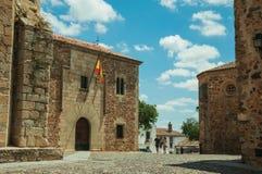 Folk som går i en kullerstengränd under gotiska byggnader på Caceres arkivbilder