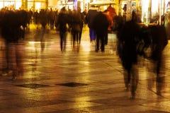 Folk som går i en shoppinggata i rörelsesuddighet på natten Arkivfoton