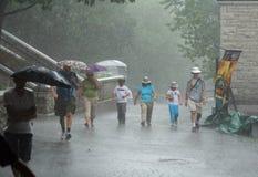 Folk som går i hårt regn Royaltyfri Foto