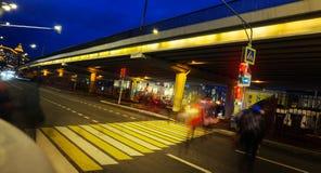 Folk som går i snabb rörelse i natten på trafikljuset, övergångsställe, nattgatabakgrund royaltyfri fotografi