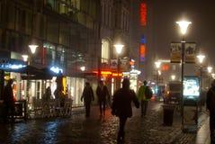 Folk som går i staden på en dimmig natt Royaltyfri Fotografi