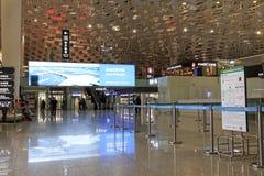 Folk som går inom Shenzhen Bao'an den internationella flygplatsen i Guandong, Kina Arkivbild