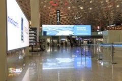 Folk som går inom Shenzhen Bao'an den internationella flygplatsen i Guandong, Kina Arkivfoto