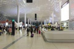 Folk som går inom Shenzhen Bao'an den internationella flygplatsen i Guandong, Kina Royaltyfri Bild