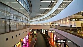 Folk som går inom terminalen av Wien den internationella flygplatsen lager videofilmer