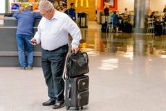 Folk som går med bagage i en flygplats Royaltyfria Bilder