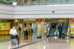 Folk som går med bagage i en flygplats Royaltyfri Bild
