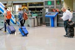 Folk som går med bagage i en flygplats Arkivfoto