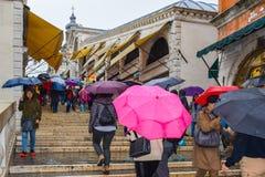 Folk som går med paraplyer på trappuppgång av den Rialto bron Ponte de Rialto i Venedig, Italien royaltyfri fotografi