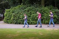 Folk som går med smartphones royaltyfri foto