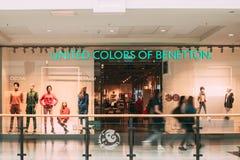 Folk som går nära eniga färger av det Benetton lagret i shopping arkivbilder