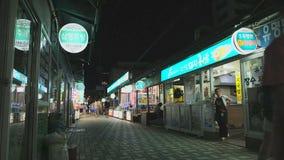 Folk som går nära marknadsgatan på det Haeundae området, Busan, Sydkorea, 10 Juli 2017 stock video