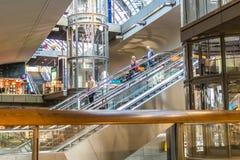 Folk som går ner rulltrappan i Berlin Hauptbahnhof järnvägstatio Royaltyfri Foto