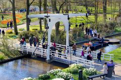 Folk som går på bron över vattenkanalen i den härliga Keukenhof trädgården, Holland arkivfoto